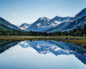 Windless day provided a smooth lake as a mirror for a snow capped mountain.